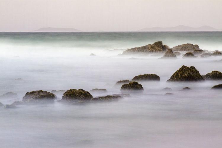 Movimiento de las olas al chocar con las piedras, al fondo los frailes