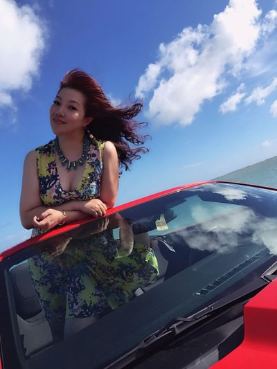 Portrait of woman peeking from car roof against blue sky