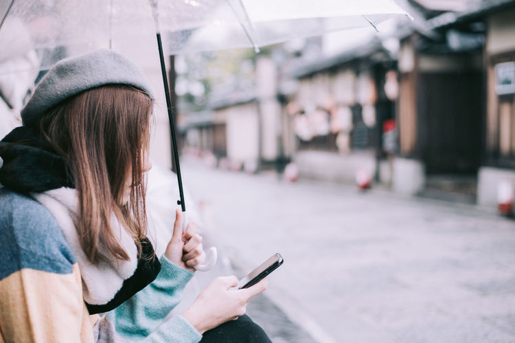 Woman using mobile phone and holding umbrella while standing outdoors
