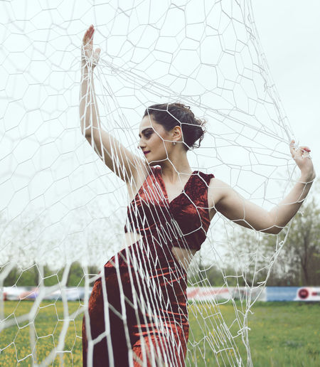 Beautiful young woman posing by net on playing field