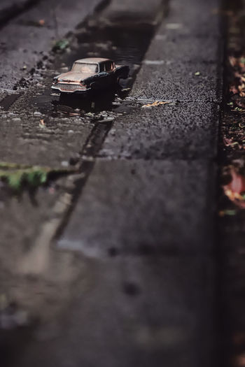 Toy Toy Car Vintage Cars Vintage Vintage Car Wet Puddle Reflection Paving Stone Creative Creativity Creative Photography Selective Focus Day Footpath Street No People City Transportation Road Nature Outdoors Architecture High Angle View Surface Level Mode Of Transportation Close-up Abandoned Sunlight Direction Land Vehicle Asphalt
