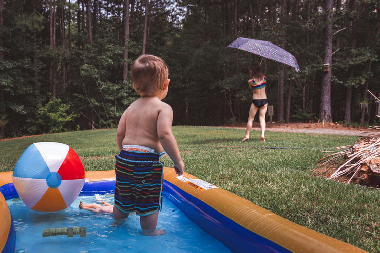 A little boy stands in a backyard kiddie pool. his sister plays with an umbrella and a sprinkler.