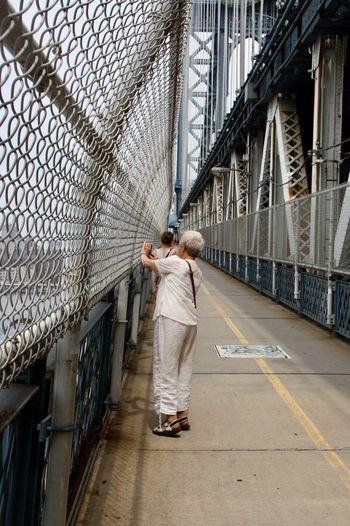 Woman standing on bridge in city