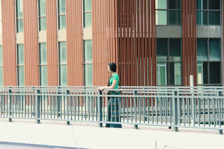Woman standing on bridge against building