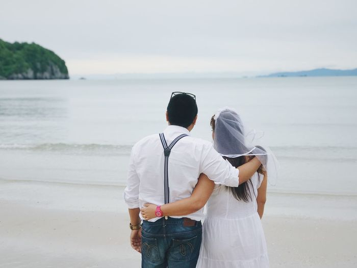 Rear view of couple standing at beach against sky