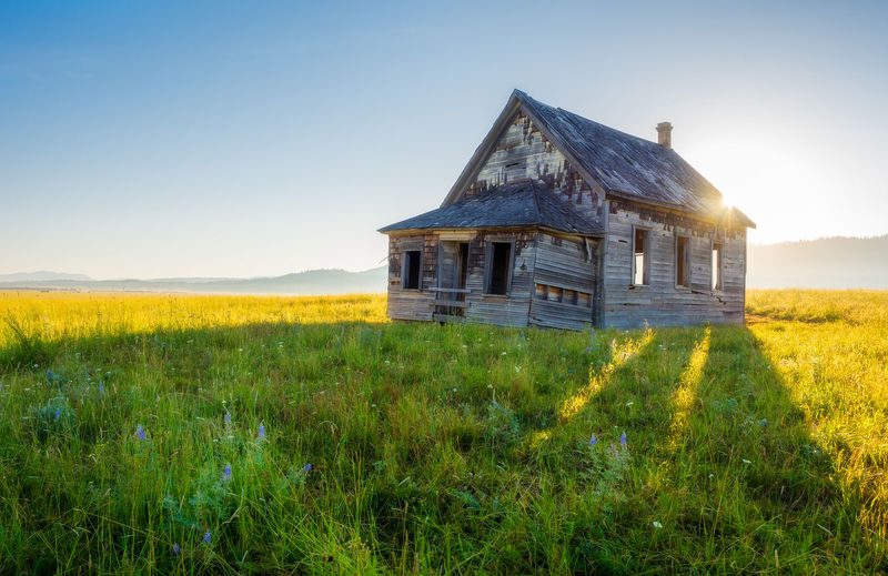 Abandoned house on field against clear sky
