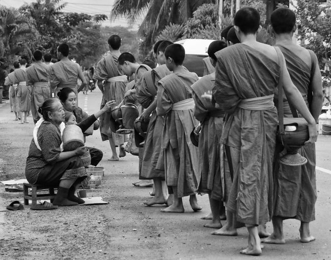 Alms giving in world heritage listed Luang Prabang, Laos Blackandwhite Photography Streetphoto_bw Streetlife Streetphotography Buddhist Monks Laos Luangprabang World Heritage Alms Giving Large Group Of People Men Togetherness Real People Day Sitting Outdoors Lifestyles People