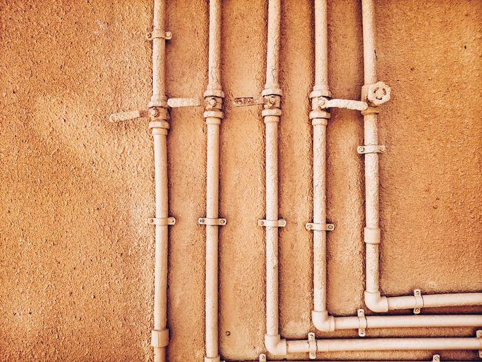 Pipes On Brown Wall