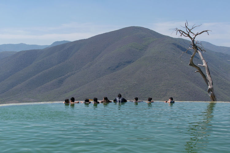 People Swimming In Infinity Pool Against Sky