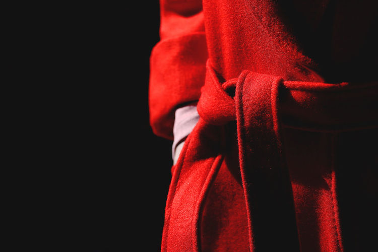 Midsection of person wearing red bathrobe against black background