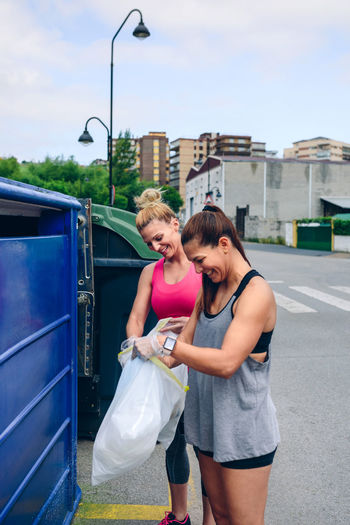 Young woman putting garbage in bin while standing on footpath