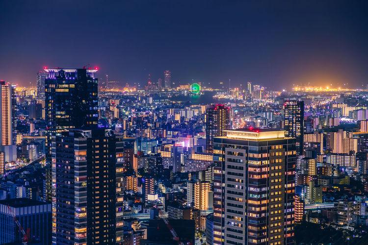 High angle view of illuminated osaka city buildings against sky
