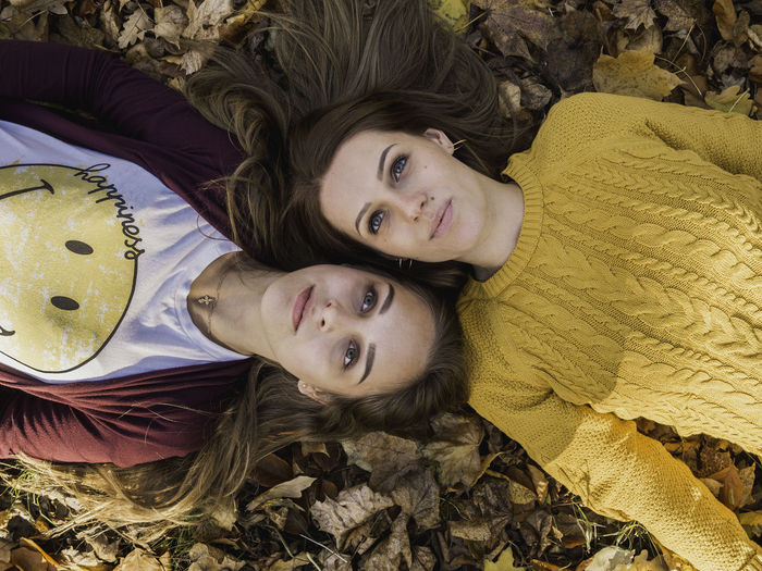 Human Connection Sisters Fall Fall Beauty Looking At Camera Portrait Two People Child High Angle View Lying Down Women Girls Casual Clothing Togetherness Lifestyles Bonding Emotion Leisure Activity Females Smiling Real People Positive Emotion Innocence Sister Childhood Hairstyle