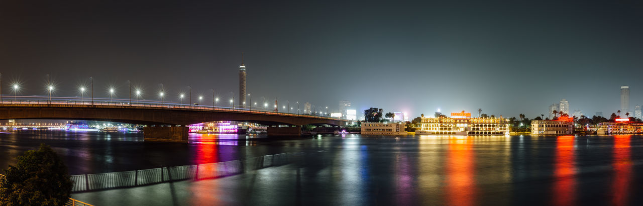 Panoramic of Cairo city center at night, long exposure with smoothed out water. Architecture Built Structure Night Reflection Illuminated Bridge Water Building Exterior City Travel Destinations Connection Transportation River Sky Long Exposure Nature Waterfront Outdoors Cityscape Skyscraper Cairo Egypt Zamalek