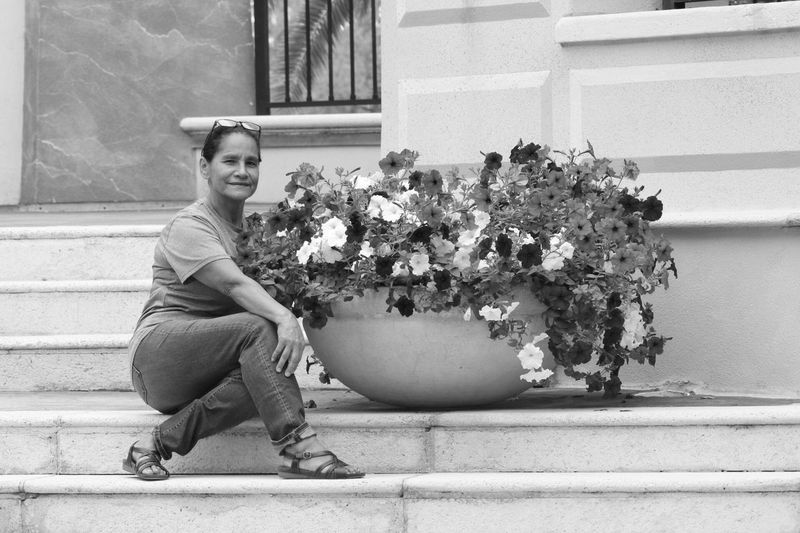 OswaldoV Streetphotography Flower Sitting Plant Full Length One Person Real People Young Adult Outdoors Building Exterior Young Women Growth Day Lifestyles Nature Happiness Portrait Smiling Architecture Freshness Adult Black And White Canonphotography EyeEmNewHere