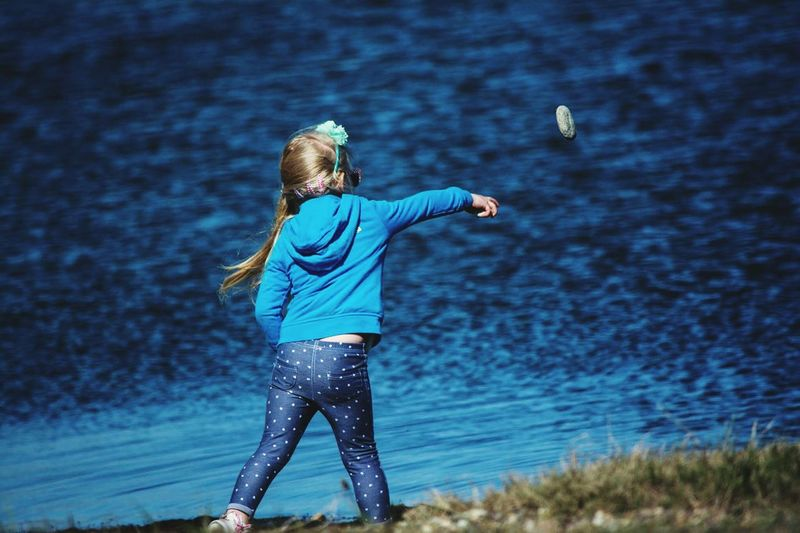Rear View Of Girl Throwing Pebble