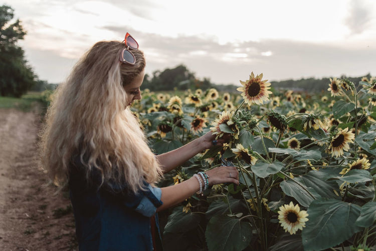 Woman standing by flowering plants on field against sky