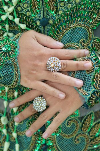Midsection of woman in green dress wearing rings