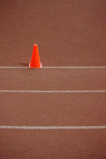 High angle view of red traffic cone on running track