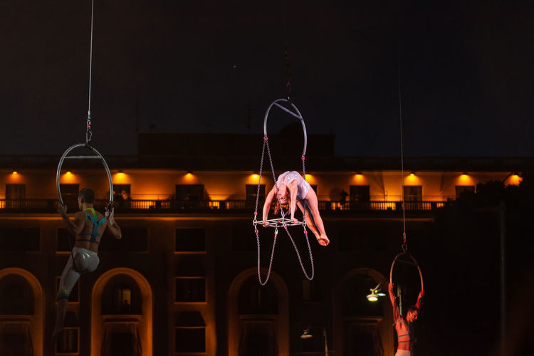 Illuminated lighting equipment hanging against sky at night