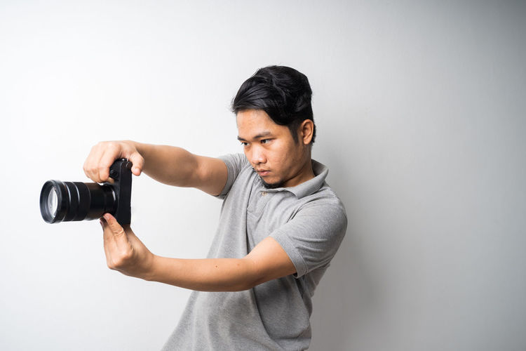 Young man holding camera over white background