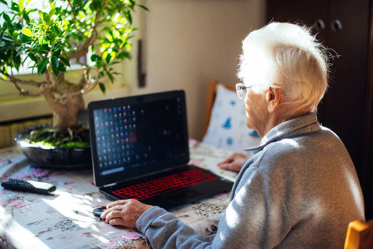 Rear view of senior woman using laptop while sitting at home