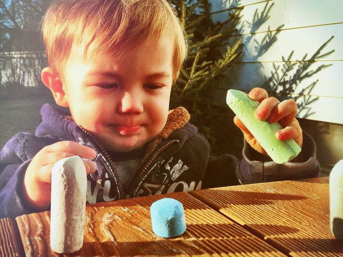 Close-up of innocent boy playing with chalks at wooden table