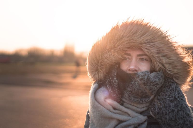 Close-Up Of Woman Wearing Warm Clothing Against Sky During Sunset