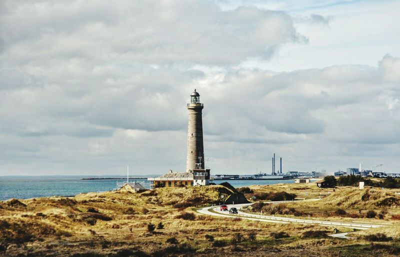 Lighthouse on shore by sea against cloudy sky