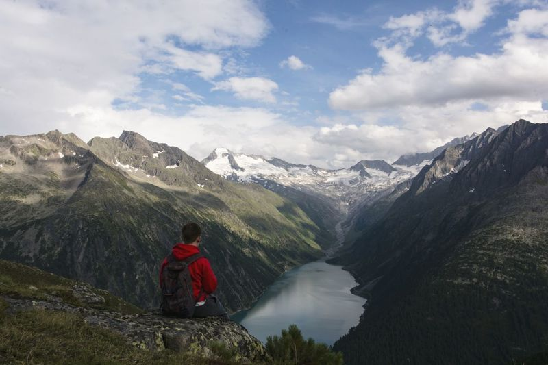 Man looking at mountains against sky