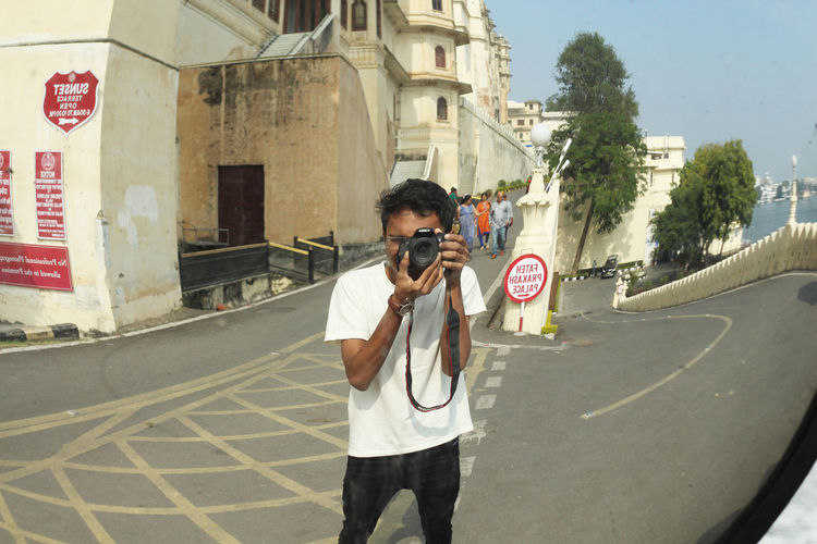 a Photographer trying to capture his self in the curved mirror at udaipur, Rajsthan. Architecture Building Exterior Built Structure Casual Clothing City Citypalace Citypalaceudaipur Day Front View Leisure Activity Lifestyles Looking At Camera Men One Person Outdoors People Real People Sky Standing Udaipur Young Adult