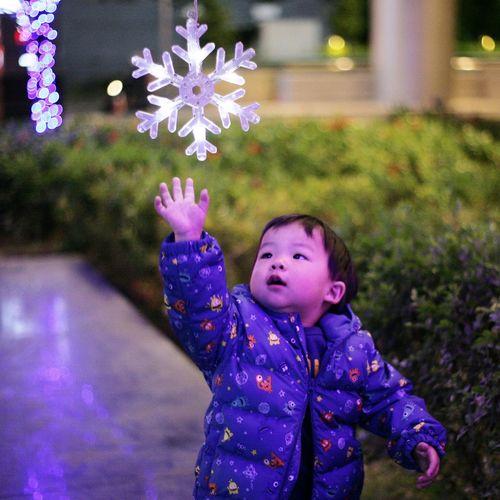 Cute boy touching illuminated touching lighting equipment
