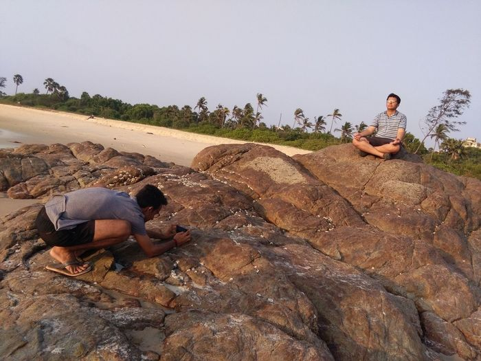 Man photographing friend sitting in lotus position on rock formation at beach against sky
