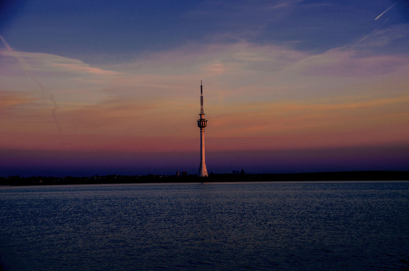 Communications tower against sky at sunset
