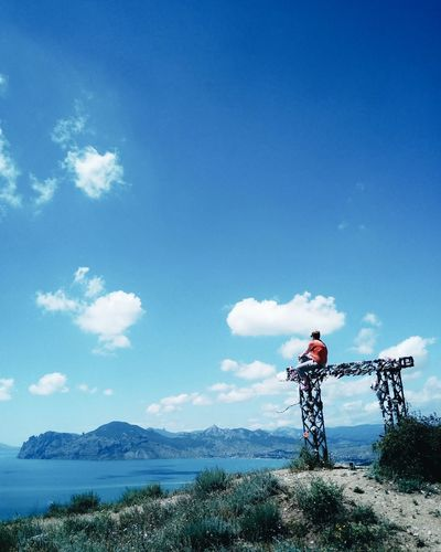 Man Sitting On Built Structure By Sea Against Blue Sky