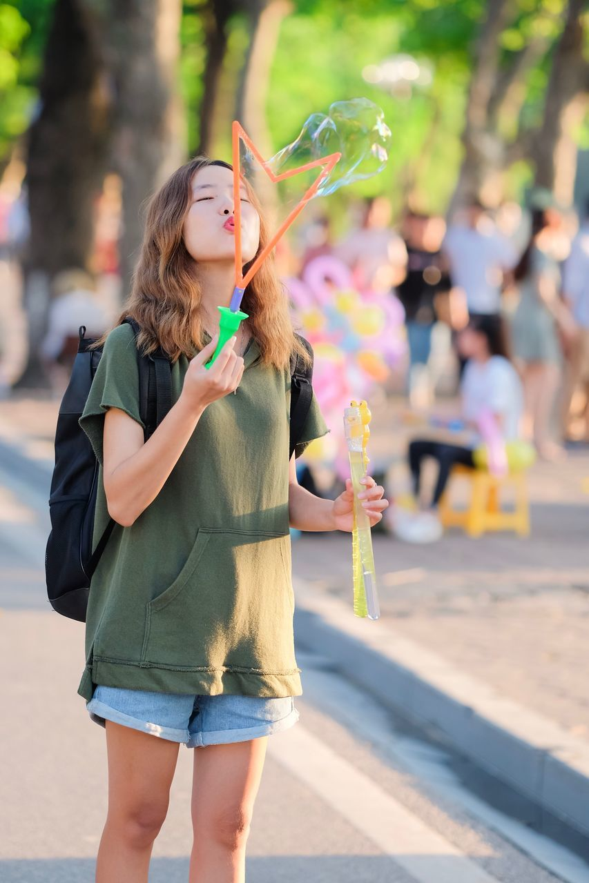 real people, leisure activity, casual clothing, one person, front view, three quarter length, focus on foreground, outdoors, bubble wand, lifestyles, happiness, fun, standing, day, young women, smiling, young adult, beautiful woman, multi colored