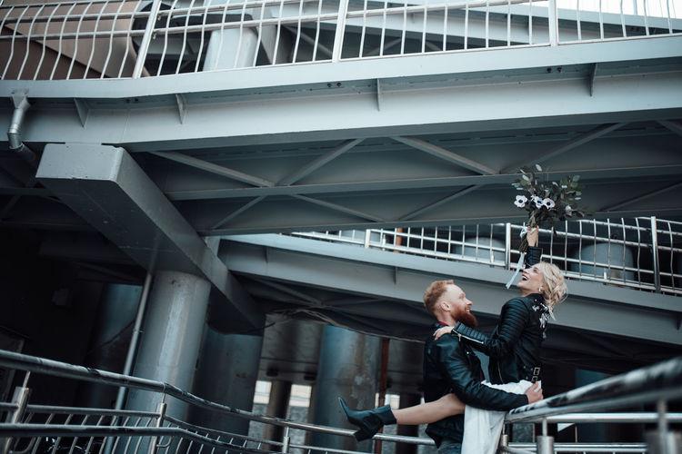 Full length of men standing on railing in city