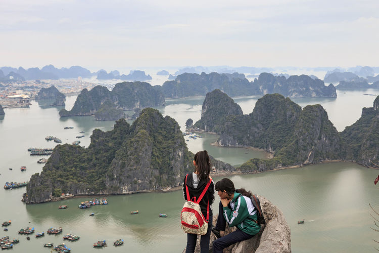 Halong Bay, Vietnam - February 24, 2016: Young couple looking at Halong Bay and city from the top of Bai Tho Mountain ASIA Bay Beauty In Nature Casual Clothing Cliff Day Ha Long Indochina Landscape Leisure Activity Lifestyles Mountain Nature Rock Scenics Sea Seascape Sitting Sky Southeastasia Tourism Tourist Vacations Vietnam Water