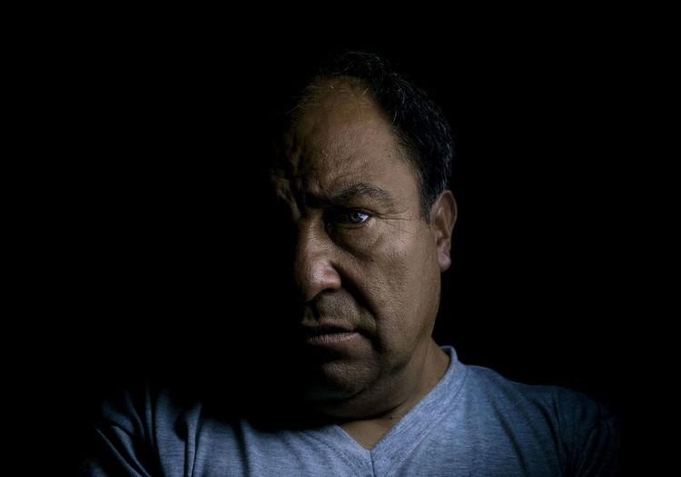 Portrait Of Senior Adult Man Over Black Background