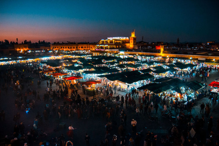 High angle view of crowd at illuminated market during night