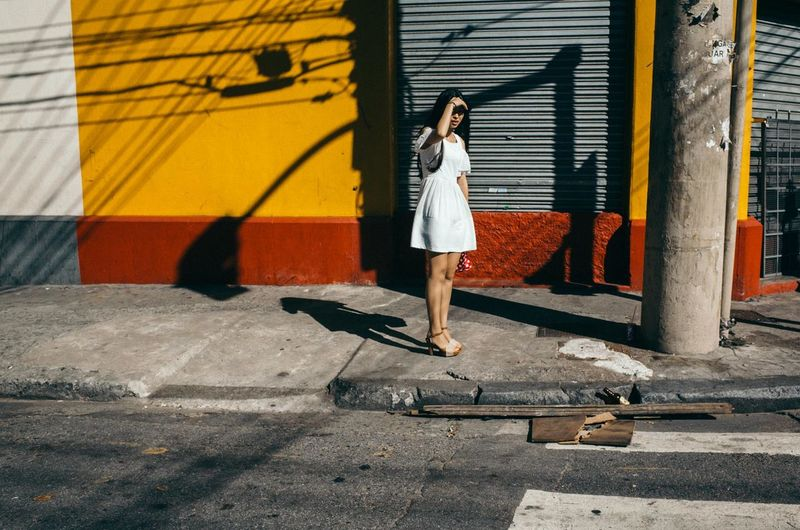 Woman in white dress is blocking the sun from her face at a street in São Paulo, Brazil The Art Of Street Photography City Young Women Full Length Women Shadow Fashion Ghetto City Life Parking Garage Graffiti Street Scene Building