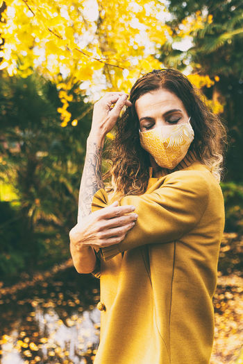 Mature woman wearing mask standing against autumn leaves