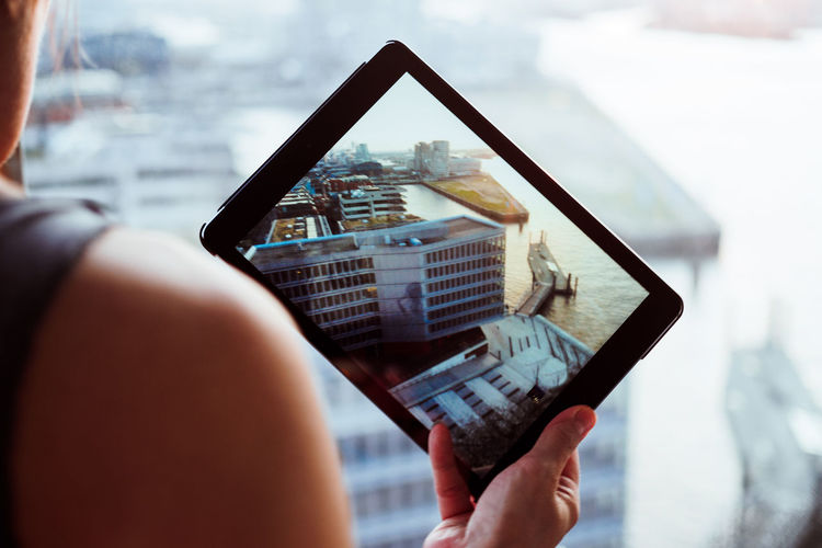 Cropped Image Of Woman Photographing With Digital Tablet