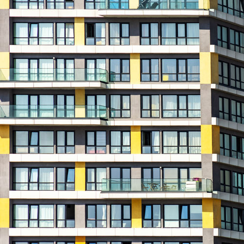 Detail of a monotonous ugly skyscraper in a suburban area . Apartment Architecture Backgrounds Balcony Building Building Exterior Building Feature Built Structure City Day Full Frame Glass - Material Modern Nature No People Outdoors Pattern Residential District Sunlight Window Yellow