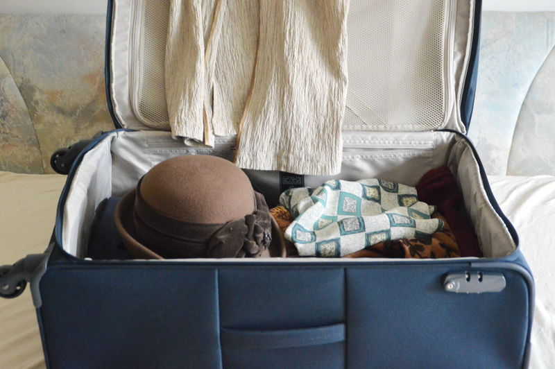 Close-up of hat and fabrics in luggage