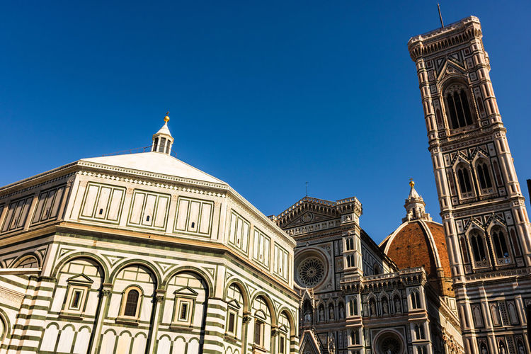 Low angle view of duomo santa maria del fiore against clear blue sky in city