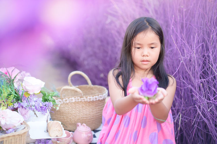 Portrait of a girl holding pink flower