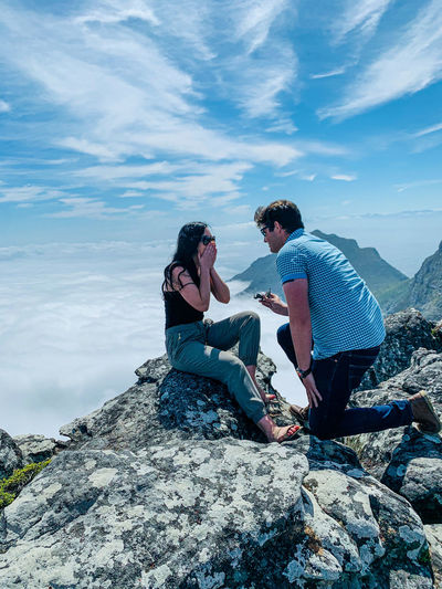 Man proposing woman while siting on mountain against sky