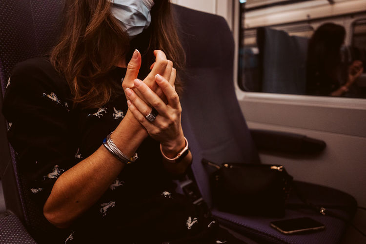 Midsection of woman using mobile phone in bus