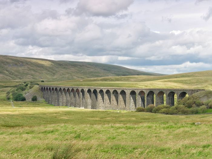 Ribblehead Viaduct. Yorkshire, UK. I missed the iconic steamtrain shot as the train arrived 10 minutes earlier than scheduled. I'm still proud of this shot though. It wasn't easy to capture the sun shining on the curve.It Wasn't Easy Than Scheduled History Grass Landscape Day Outdoors Cloud - Sky No People Mountain Beauty In Nature Nature Sky Viaduct Ribbleheadviaduct Ribblehead Viaduct Yorkshire Uk Travel Travel Destinations Architecture Railway Steamtrains